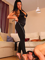 Mistress leafs through a glossy mag while her boy toy is licking her feet
